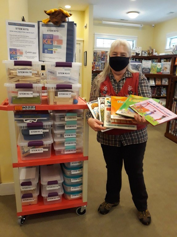 Assistant Librarian Lynn Ufer standing with STEM Kits display